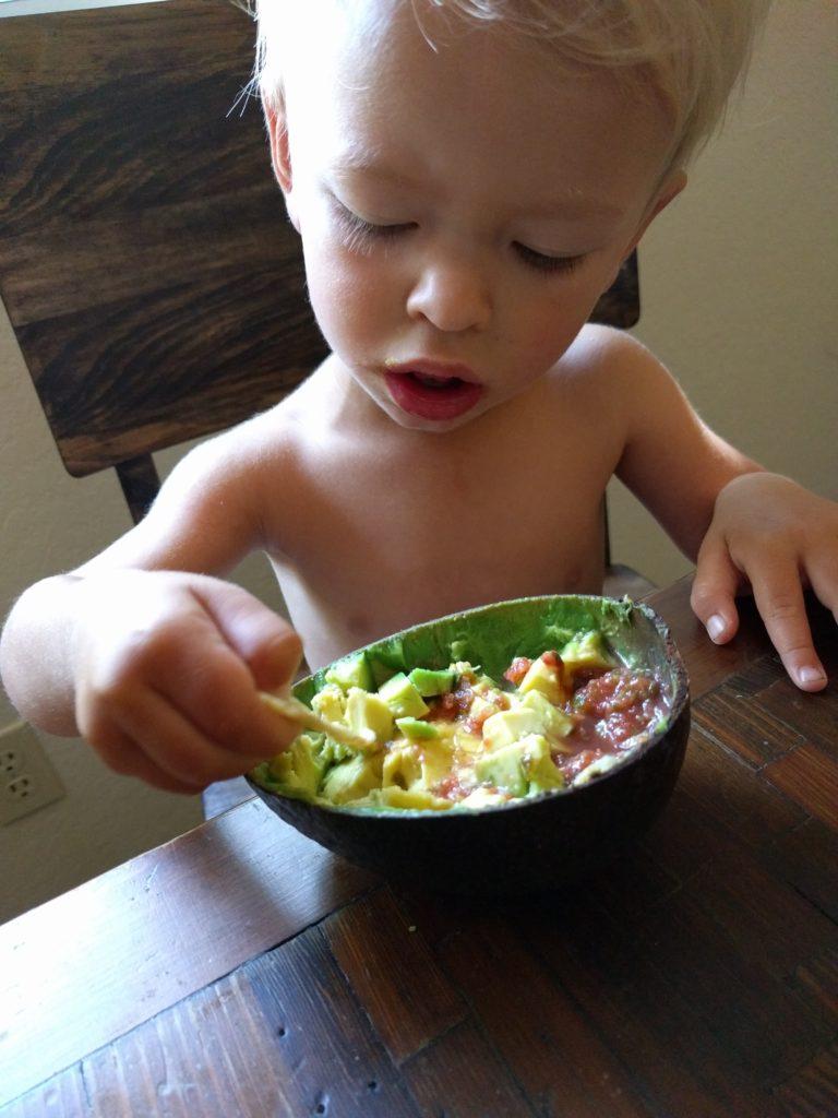 eating a Reed avocado personal bowl of guacamole